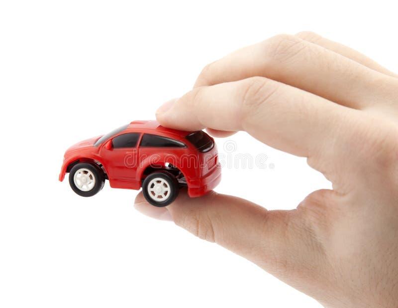 Mano que sostiene un pequeño coche rojo fotos de archivo