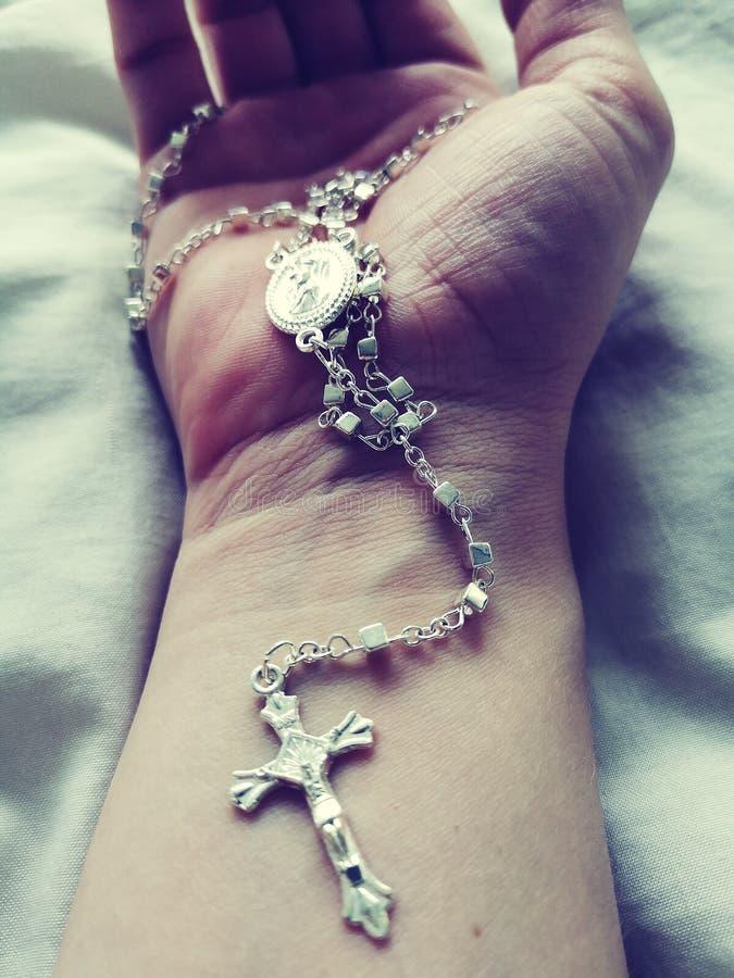 mano que sostiene un rosario en el fondo blanco fotografía de archivo libre de regalías