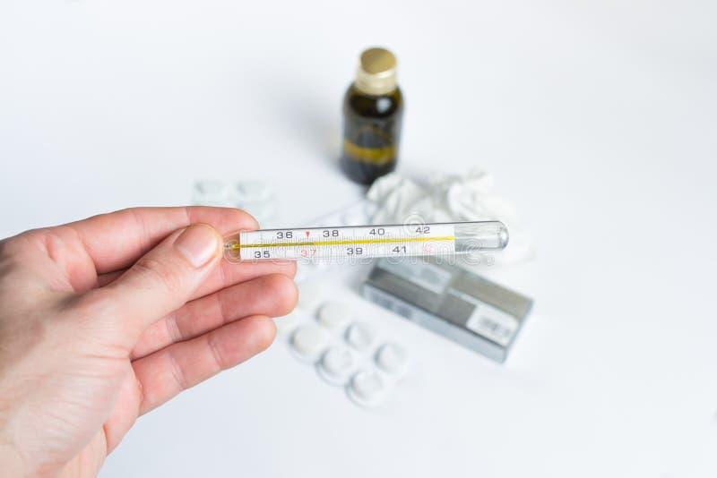 Mano que sostiene un termómetro con las píldoras y las medicaciones en backgro imágenes de archivo libres de regalías