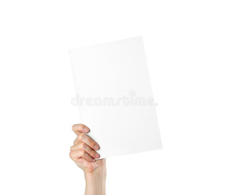 Mano que sostiene una hoja blanca en blanco del papel A4 Cierre para arriba Aislado fotografía de archivo libre de regalías