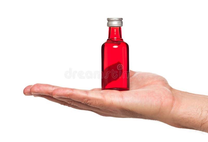 Mano que sostiene una pequeña botella fotos de archivo