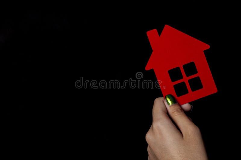 Mano que sostiene una pequeña casa de papel roja fotos de archivo libres de regalías