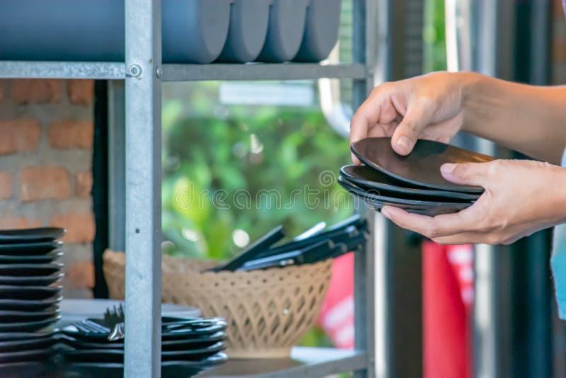 Mano que sostiene una placa negra y el estante de plato foto de archivo libre de regalías