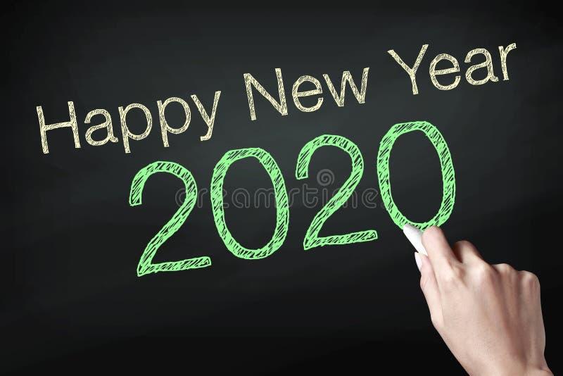 Mano que sostiene una tiza y que escribe la Feliz Año Nuevo 2020 fotos de archivo libres de regalías
