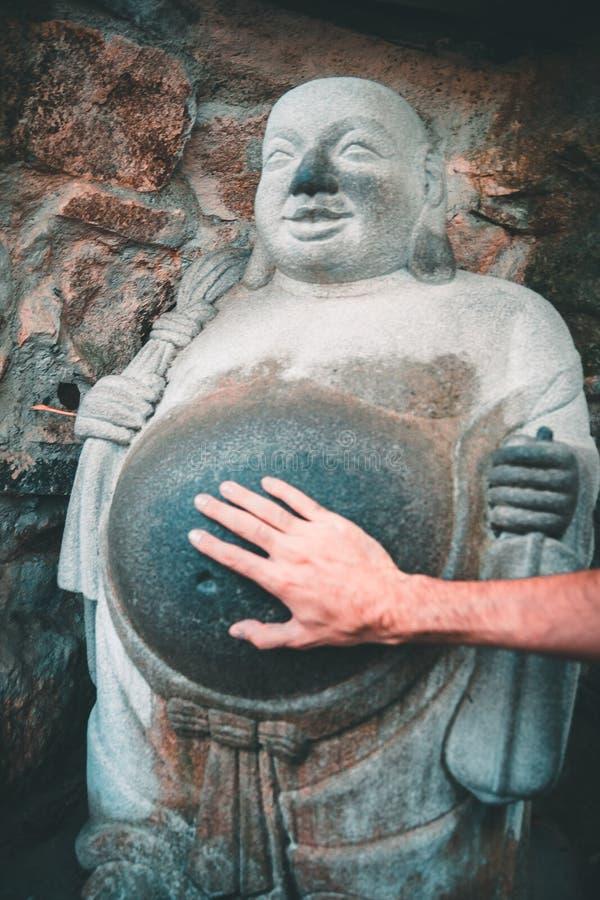 Mano que toca el vientre de una estatua de risa de Buda en el templo budista de Yonggungsa en Busán, Corea del Sur foto de archivo libre de regalías