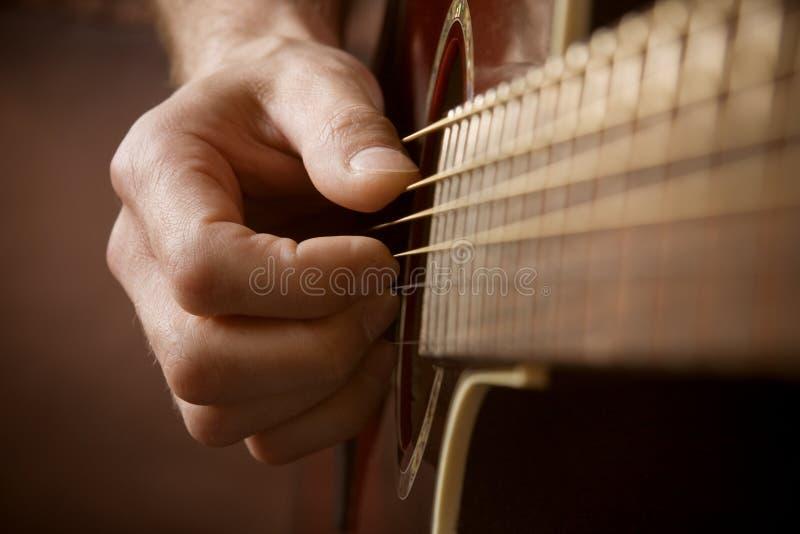 Mano que toca la guitarra acústica fotos de archivo libres de regalías