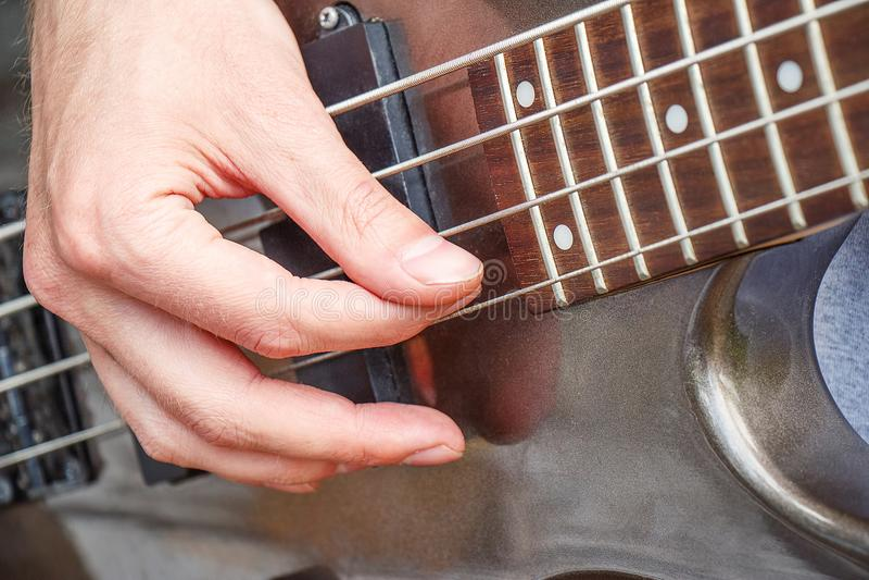 Mano que toca la guitarra eléctrica, primer fotos de archivo