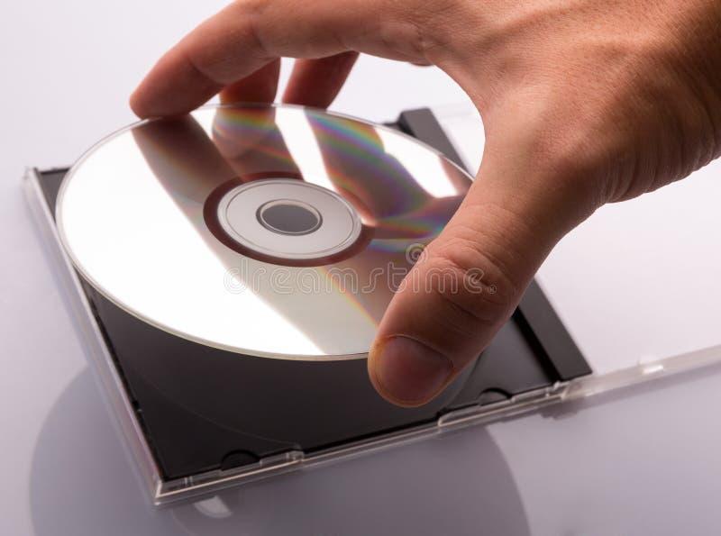 Mano que toma el disco del DVD foto de archivo libre de regalías