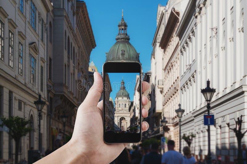 Mano que toma la foto del destino famoso de la señal y del viaje en Budapest, Hungría por el teléfono elegante móvil imagenes de archivo