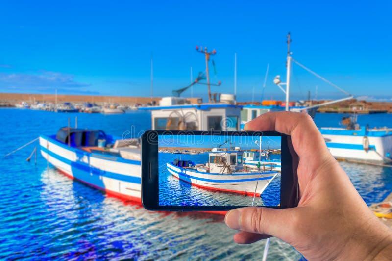 Mano que toma la imagen con un smartphone de un barco de pesca en el puerto en verano foto de archivo