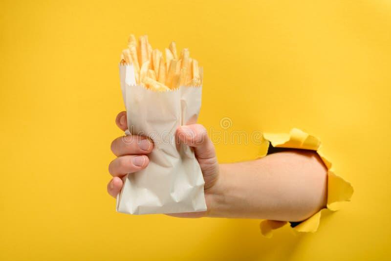 Mano que toma las patatas fritas foto de archivo