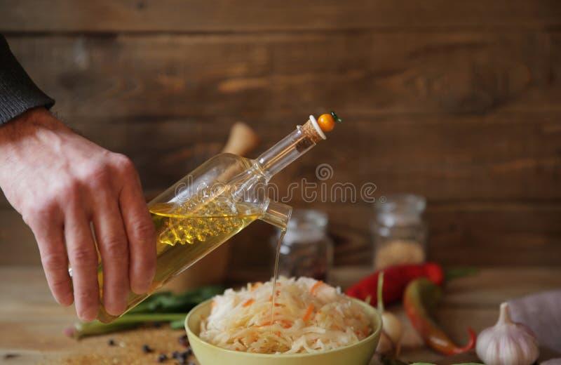 Mano que vierte el aceite de oliva en un cuenco de chucrut en una tabla de madera con las especias y las hierbas imagenes de archivo