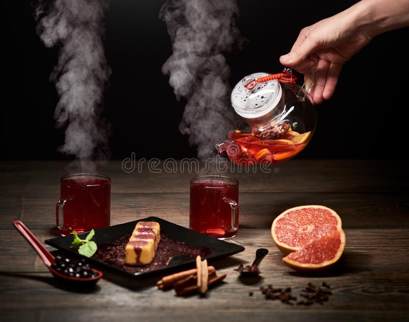 Mano que vierte t? caliente de la caldera de cristal Cocido al vapor de t? al vapor en vidrios Postre dulce japon?s delicioso en  fotografía de archivo libre de regalías