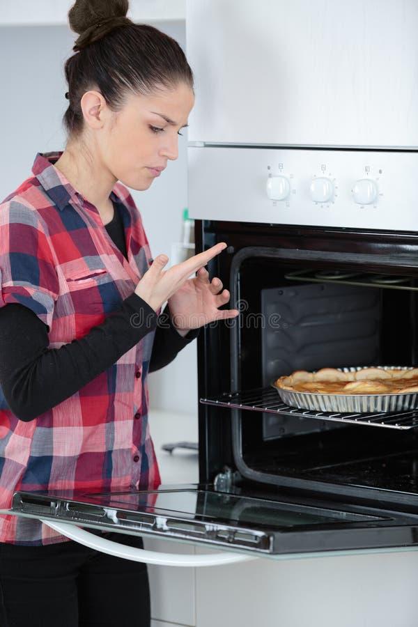 Mano quemada de la mujer joven mientras que cocina foto de archivo libre de regalías