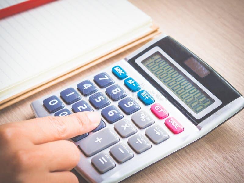 Mano retra de la mujer que trabaja con la calculadora, el lápiz rojo y el cuaderno en la tabla de funcionamiento fotografía de archivo