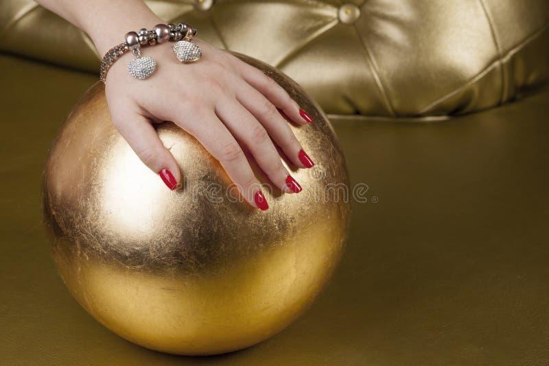 Mano rossa del chiodo su una palla dorata fotografie stock