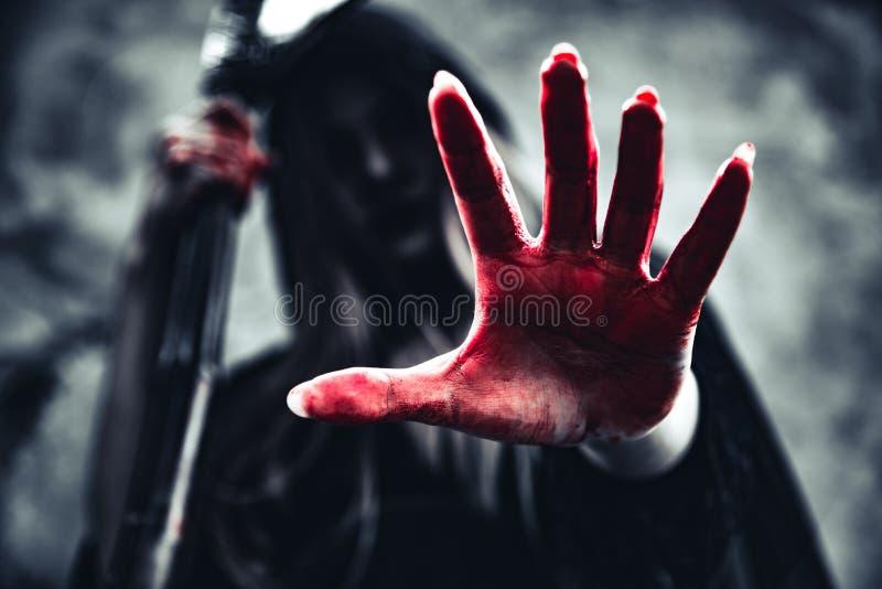 Mano sangrienta de la demostraci?n de la bruja con el segador ?ngel femenino del demonio en ropa y capilla negras en fondo de la  imagen de archivo