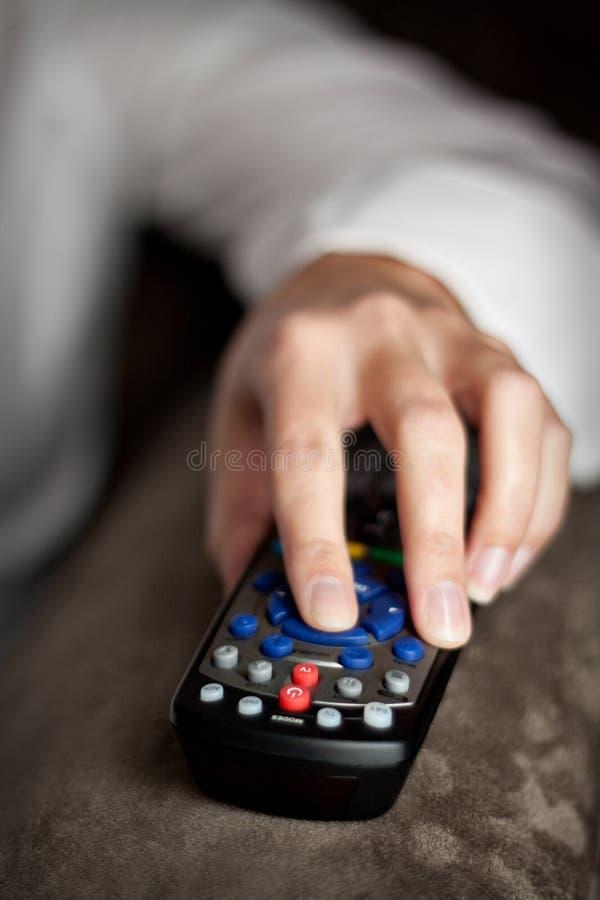 Mano sinistra che giudica una TV telecomandata fotografia stock