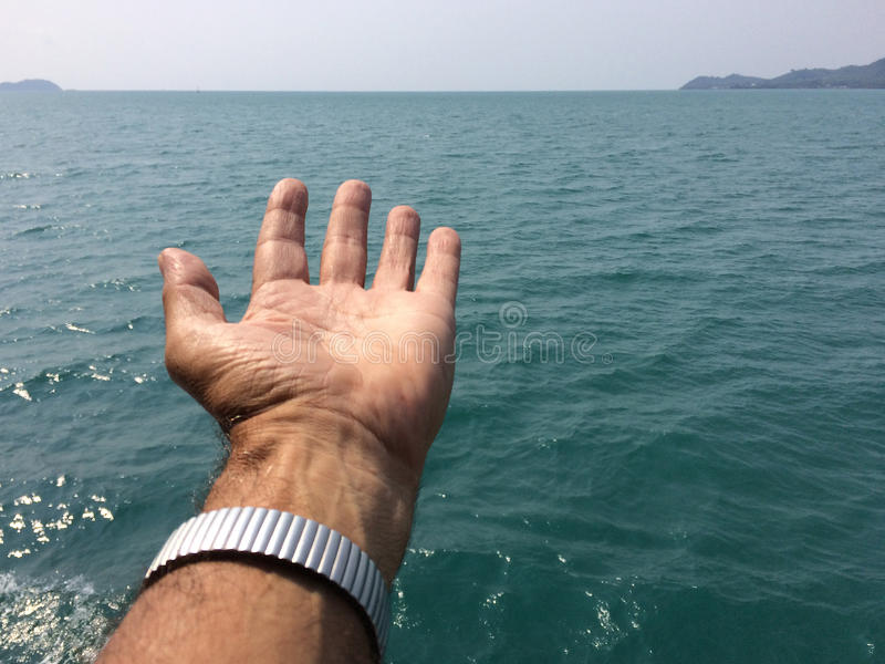 Mano sobre el mar fotografía de archivo