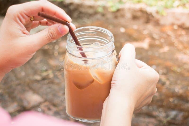 Mano sobre el vidrio de café helado de la leche con efecto del filtro del vintage foto de archivo libre de regalías
