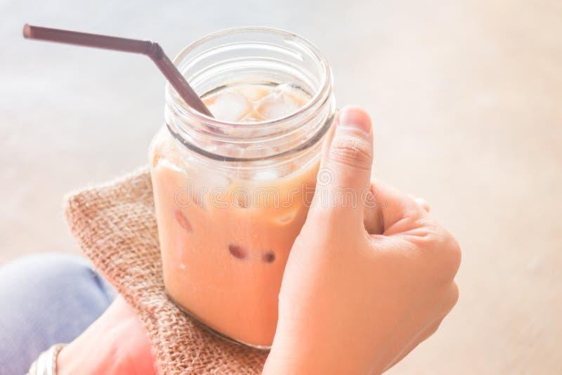 Mano sobre el vidrio de café helado de la leche con efecto del filtro del vintage imagen de archivo