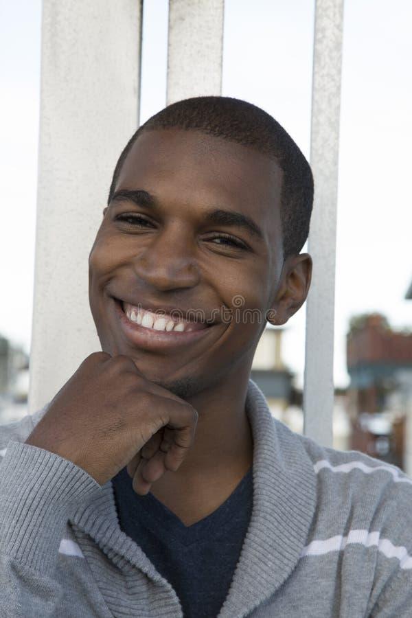 Mano sonriente modelo masculina afroamericana en su barbilla fotos de archivo