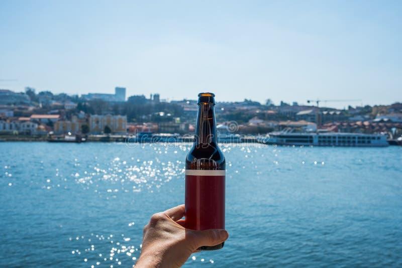 Mano sosteniendo una botella genérica de cerveza en Oporto, Portugal imagen de archivo