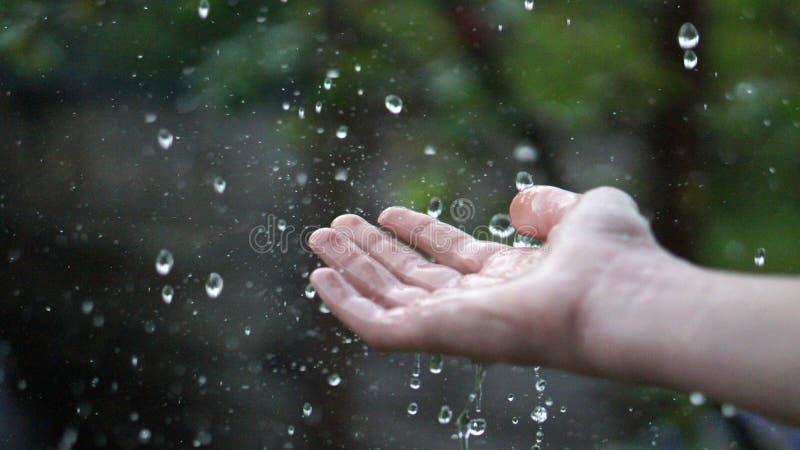 Mano sotto la pioggia immagine stock