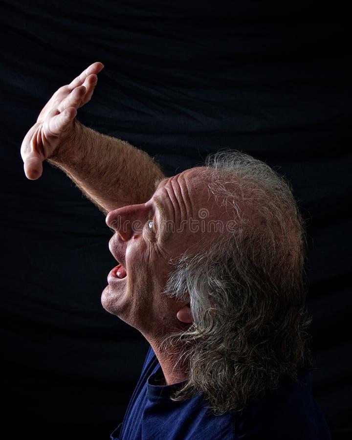 Mano spaventata della holding dell'uomo in su fotografia stock libera da diritti