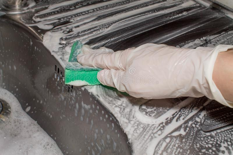 Mano in spolveratore del guanto del lattice che lava il lavandino del metallo Pulizia fotografie stock libere da diritti