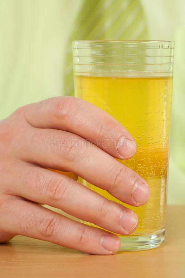 Mano su un vetro con la bevanda fresca immagine stock