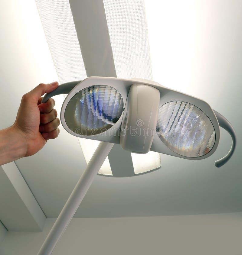 Mano su una lampada in una clinica dentaria immagini stock libere da diritti