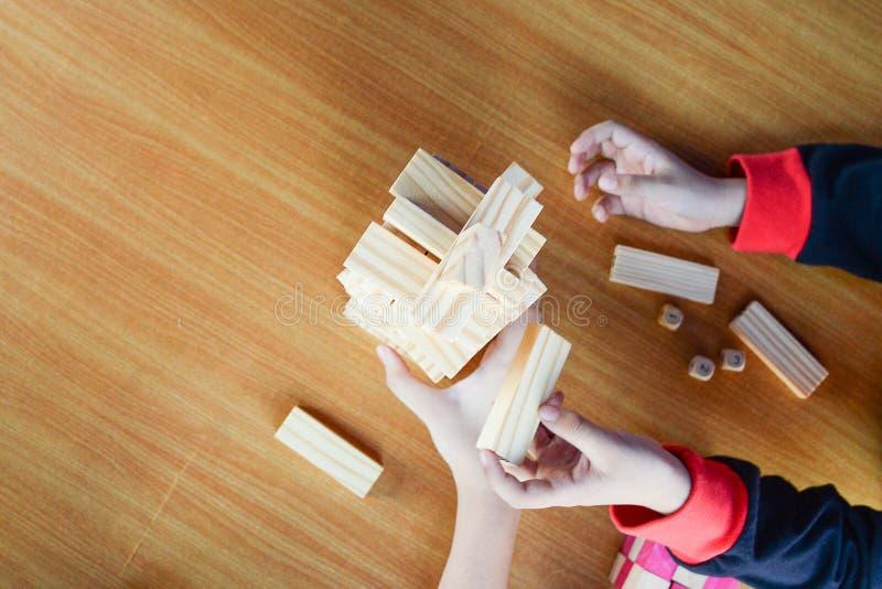Mano suave del foco del muchacho asiático y su de la hermana felices de jugar al juego de madera de los bloques en la tabla de ma imagenes de archivo
