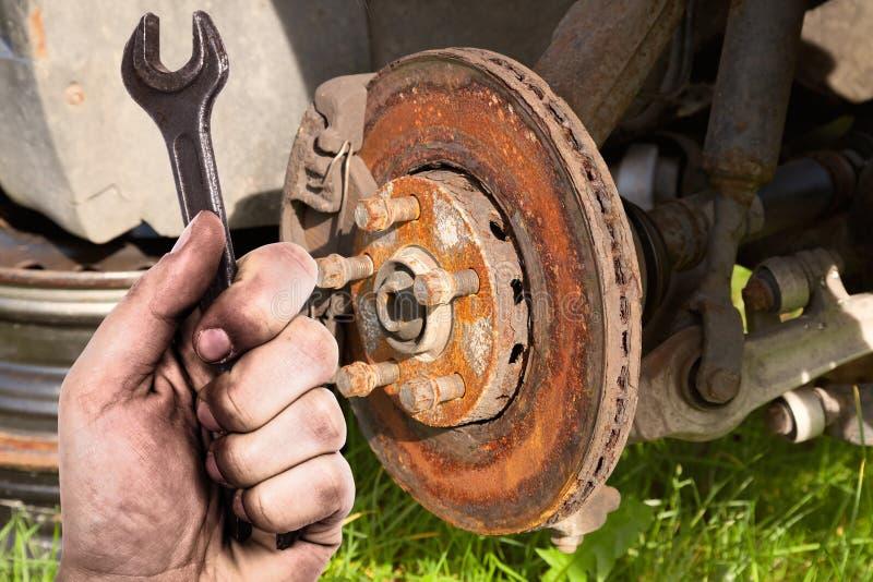 Mano sucia que sostiene la llave El mecánico está reparando los frenos en un vehículo de pasajeros imagen de archivo