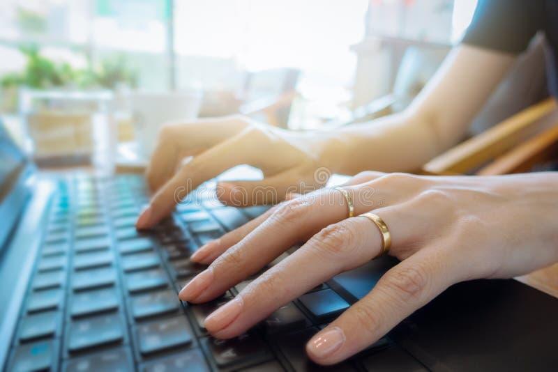 Mano sulla fine della tastiera su, donna di affari che lavora al computer portatile nella h fotografia stock libera da diritti