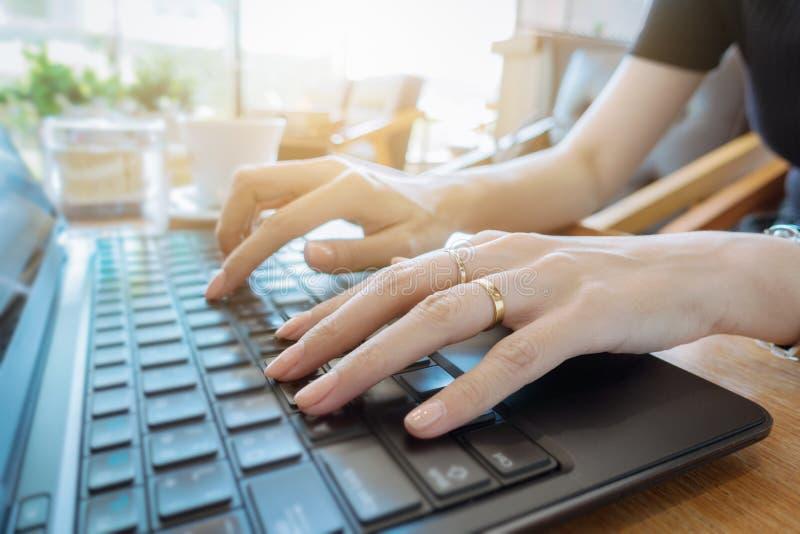 Mano sulla fine della tastiera su, donna di affari che lavora al computer portatile nella h immagini stock