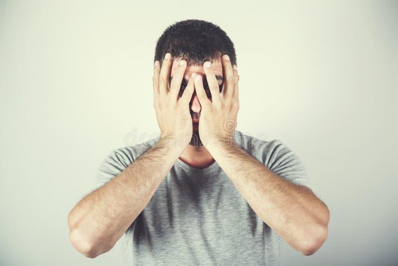 Mano triste del hombre en cara foto de archivo libre de regalías