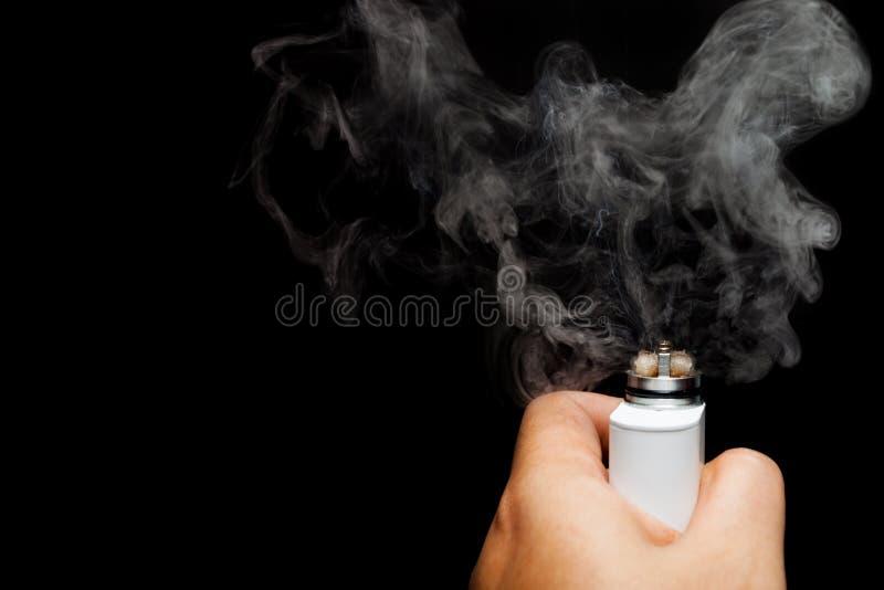 Mano umana asiatica che tiene sigaretta elettronica fotografia stock libera da diritti
