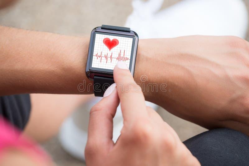 Mano umana che indossa orologio astuto che mostra tasso di battito cardiaco fotografie stock