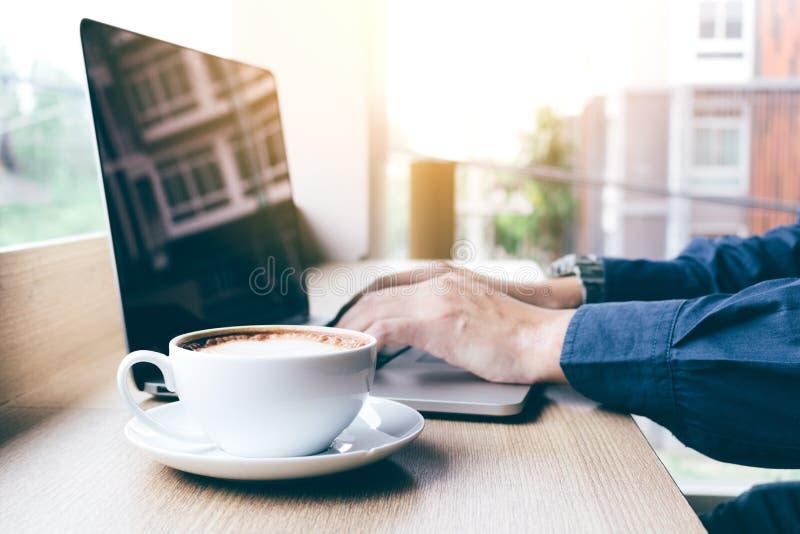 Mano umana che lavora al computer portatile della tastiera con caffè nella mattina immagini stock