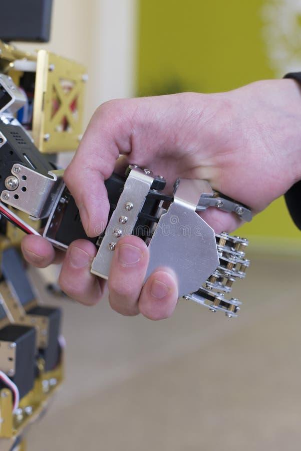 Mano umana che tiene una mano del robot con una stretta di mano fotografia stock libera da diritti