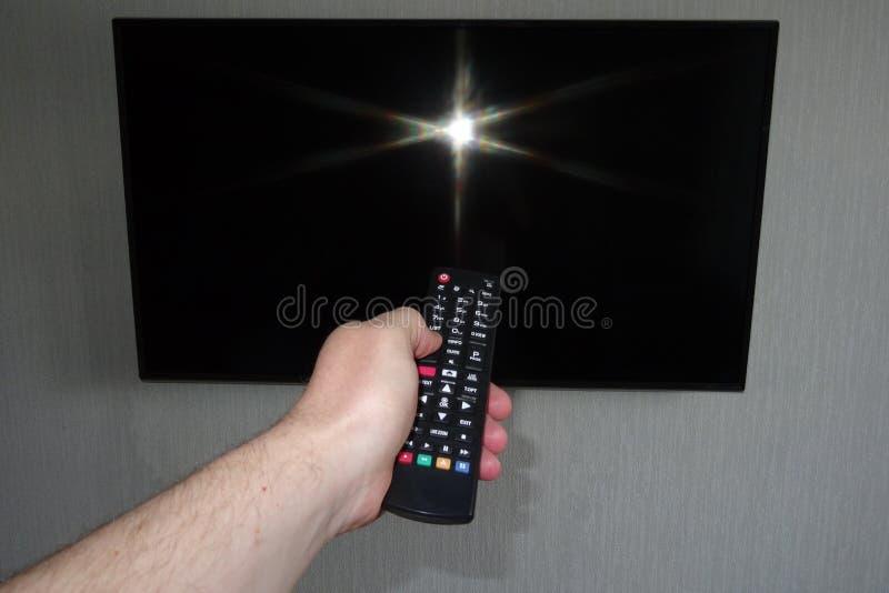 Mano umana con un telecomando davanti ad un ghiaccio nero della TV fotografia stock
