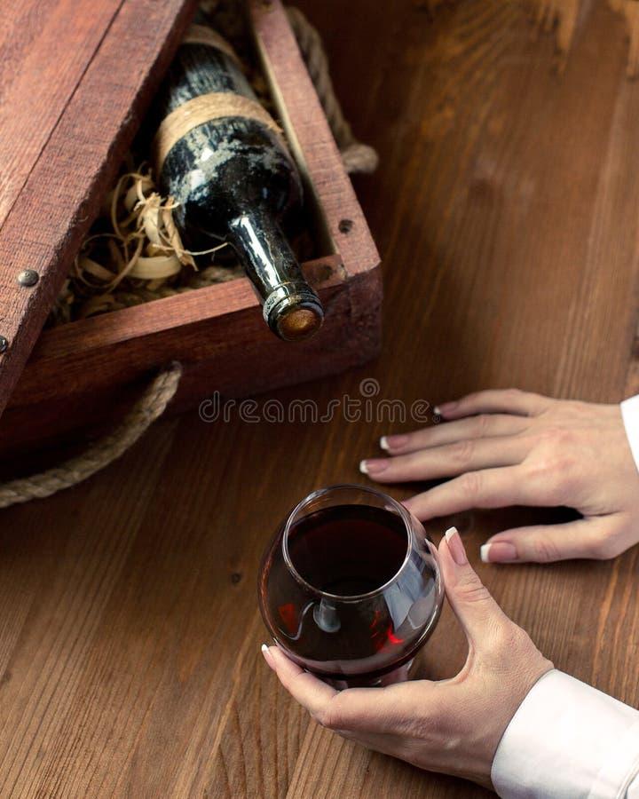 Mano umana con una tazza di vino rosso Vecchio imbottigli la cassa d'annata fra legno che si rade sul fondo di legno, fuoco selez fotografie stock