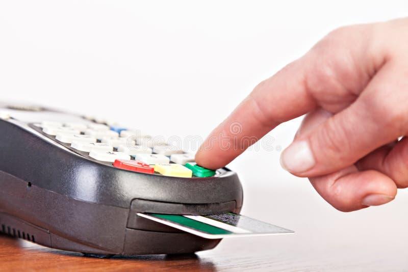 Mano umana facendo uso del terminale di pagamento, lettore della carta di credito fotografia stock