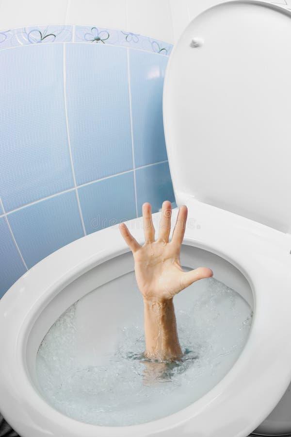 Mano umana nella ciotola di sciacquone o in WC che si arrossisce e che chiede l'aiuto fotografie stock