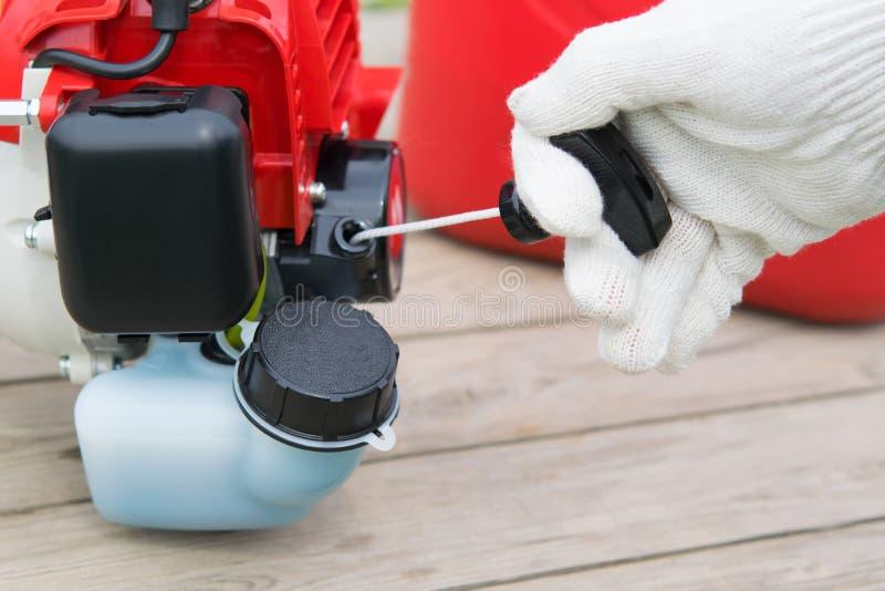 mano in un guanto protettivo, tirate il cavo per avviare il falciatore del motore a benzina fotografia stock libera da diritti