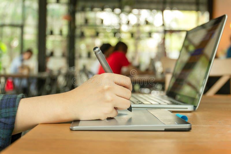 Mano usando el penand digital de la tableta y de la aguja que trabaja en el ordenador portátil fotografía de archivo libre de regalías
