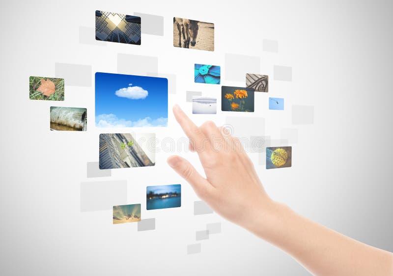 Mano usando interfaz de la pantalla táctil con los cuadros fotografía de archivo libre de regalías
