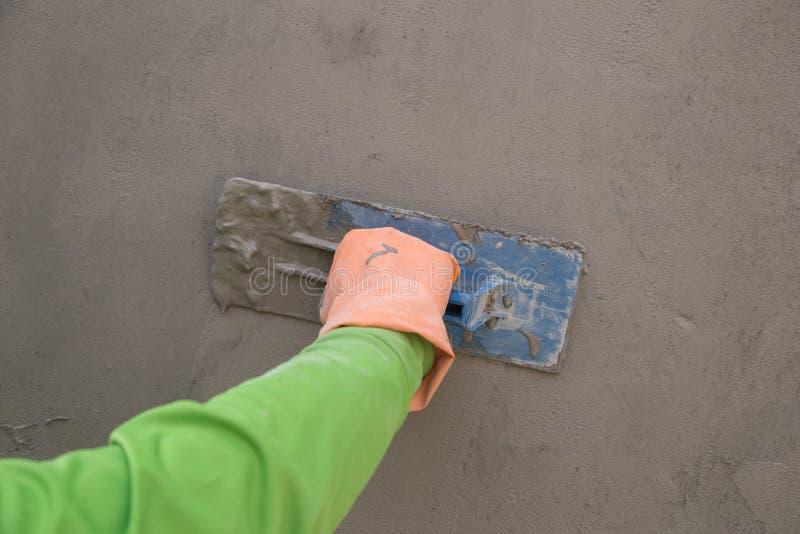 Mano usando la paleta para acabar el muro de cemento mojado en la construcción si imagen de archivo libre de regalías