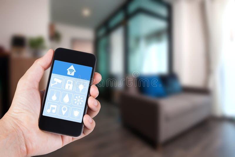 Mano usando smartphone al hogar elegante app en móvil foto de archivo libre de regalías